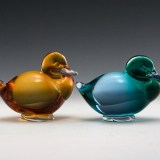 Vintage pair of Pauly & C glass resting ducks with red and white inventory label still attached.
