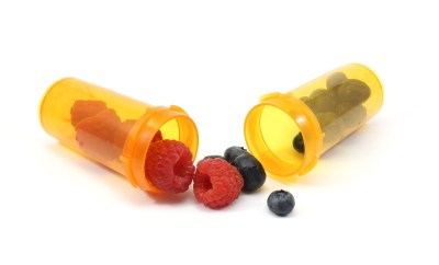 Raspberries and blueberris in pill bottles on a white background
