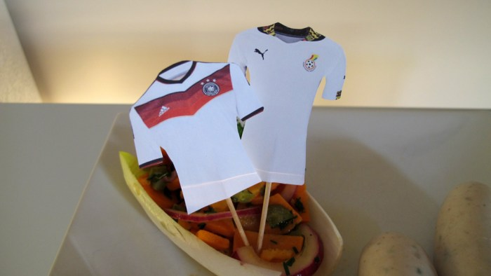 Trikot-Fähnchen der beiden Mannschaften auf Weisswürste mit Süsskartoffel-Salat