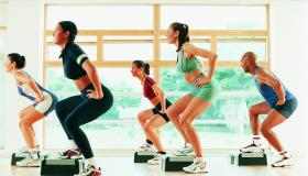 Three women in step workout class doing lateral lunges