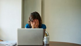 Young woman sitting at table using laptop, looking stressed