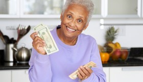 African American woman counting money in kitchen