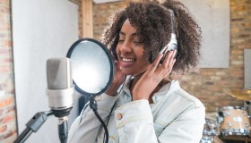 Woman singing at a recording studio