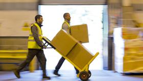 Workers carting boxes in warehouse