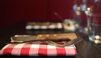 Place setting on dining table. Fork, knife and glass.