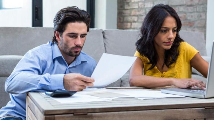 couple-in-living-room-paying-bills