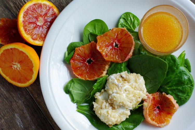 Glossy green spinach leaves topped with two discs of oozy nut crusted goat's cheese and slices of blood orange.