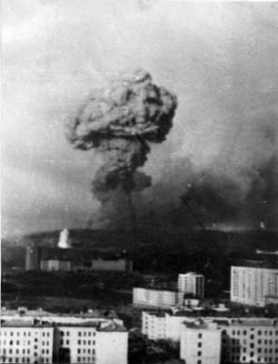 """18 мая 1984 года. Взрыв (к счастью, не ядерный) на пятом складе воинской части на Окольной - главной базе вооружений Северного флота. Тогда от матросского окурка за час-полтора была уничтожена почти половина флотского запаса стратегических ракет, торпед и мин.   Это было на исходе рабочего дня. Над заливом взлетела и по крученой траектории ушла за сопки ракета. За ней еще одна, и еще... Воздух наполнился воем, треском, грохотом разрывов. В городе, а тем более на кораблях, стоящих у причалов Североморска, сразу поняли - """"салютует"""" Окольная, гранитная стена которой возвышалась в километре от илых кварталов и в нескольких сотнях метров от кораблей 7-й эскадры. У причалов самой базы под загрузкой стояли две атомные подводные лодки.""""Салют"""" нарастал. В небе крутились уже несколько """"обезумевших"""" ракет, разлетаясь и в сторону города, и в сторону кораблей. Вскоре в небо рванул гигантский огненно-черный сноп. Медленно поднимаясь в небо, он приобретал грибообразную форму, что привело в смятение все население города.  По улицам бежали женщины с детьми на руках, многие полуодетые, в домашних халатах и тапочках; вперемешку с ними и мужчины, кое-кто в форме, что придавало картине особо жуткий драматизм. Лезли на лестницы (по-североморски, трапы), ведущие вверх, на сопки. Кто-то падал, его поднимали, хватали под руки, тащили. Машины сплошным потоком тянулись из города. Забитые до отказа, все-таки останавливались, забирали детей, которых матери буквально впихивали в чужие руки. Крик, плач, ругань - и все перекрывающий грохот и вой """"вулкана"""" Окольной. Черный, с оранжево-багровой шапкой гриб, встав во весь свой исполинский рост, замер на какое-то мгновение, качнулся на город, но потом стал медленно оседать в сторону тундры, океана.  (Вид из г. Североморска)"""
