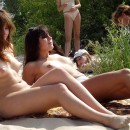 Two teen naked girls plays frisbee at the beach