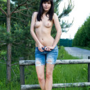 Brunette takes off clothes outdoors