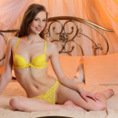 Sporty damsel in yellow undies posing on bed