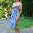 Naked girl posing with guys in the park