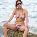 Amateur brunette wife in transparent bikini on the beach