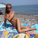 Young amateur girl resting on a nudist beach