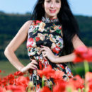 With her long black hair, striking smile, and smooth, fair skin, Lola Marron's beauty stands out as she sprawls naked in the middle of a flower field