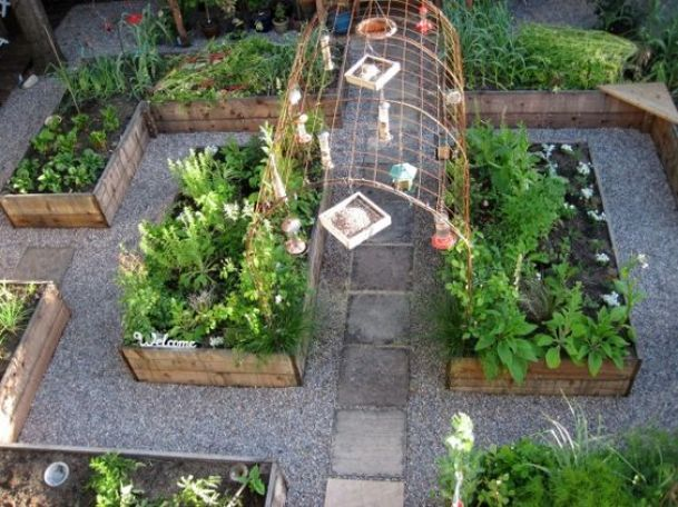 Potager, kitchen garden, raised beds, gravel paths, and an arched trellis connecting the center raised beds. from Flower Garden Girl blog.: