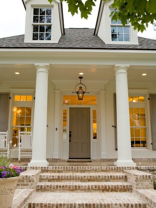 White plantation style house with soft gray and beige shutters and door with washed soft brick floor