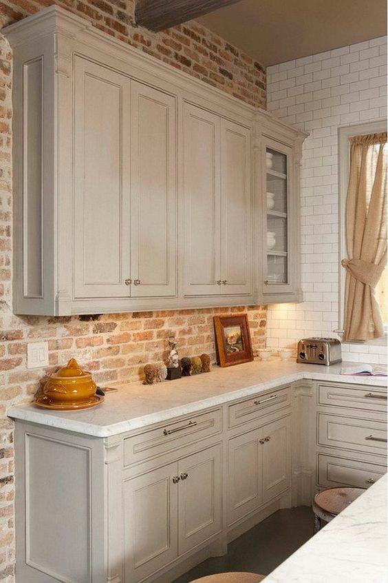 Gray Kitchen Cabinet against Brick Backsplash and White Honed Carrara Countertop: