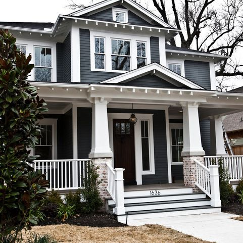 Craftsman style home with grizzle gray color and white trim dark brown door and soft washed brick on entrance columns