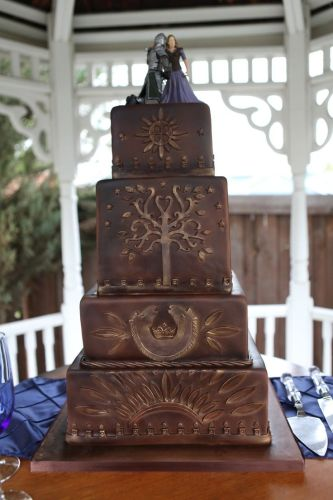 wedding cake ideas wedding ring cake topper By One Sweet Slice This wedding cake brings together Rohan and Gondor with emblems from each land plus an Eowyn Faramir topper