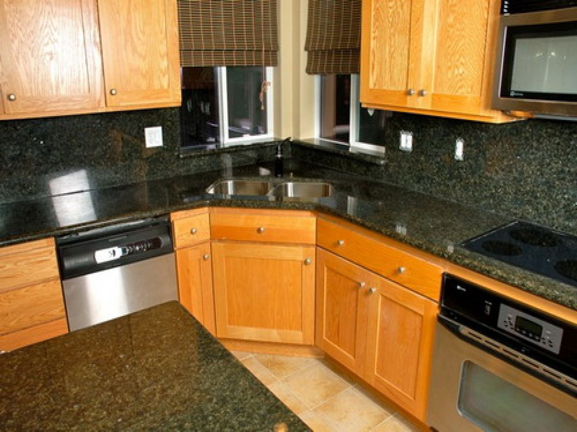 kitchen kitchen sink cabinets Fashionable Corner Kitchen Sink With Unstained Oak Kitchen Cabinet With Dark Granite Countertop As Well As Grey Wall Tiles Backsplash And Chrome Modern