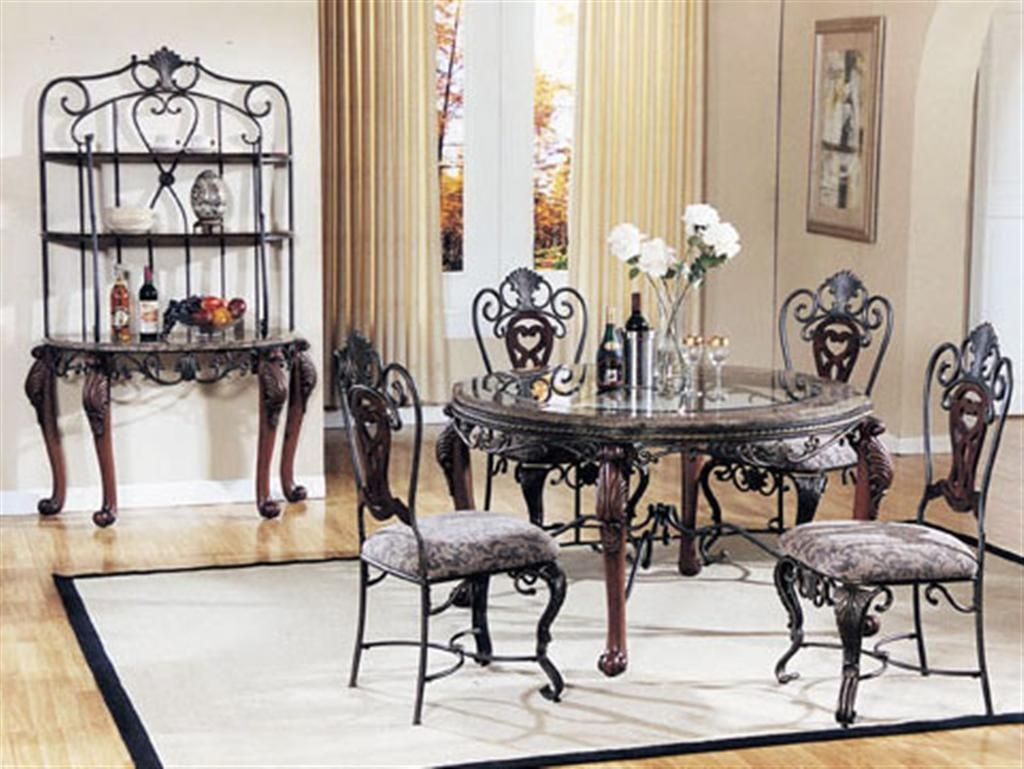 kitchen table chairs set Elegant Polished Round Teak Wooden Dining Table With Glass Table Top Black Wrought Iron Chairs with Grey Floral Pattern Padded Seat Cushion A Lovely