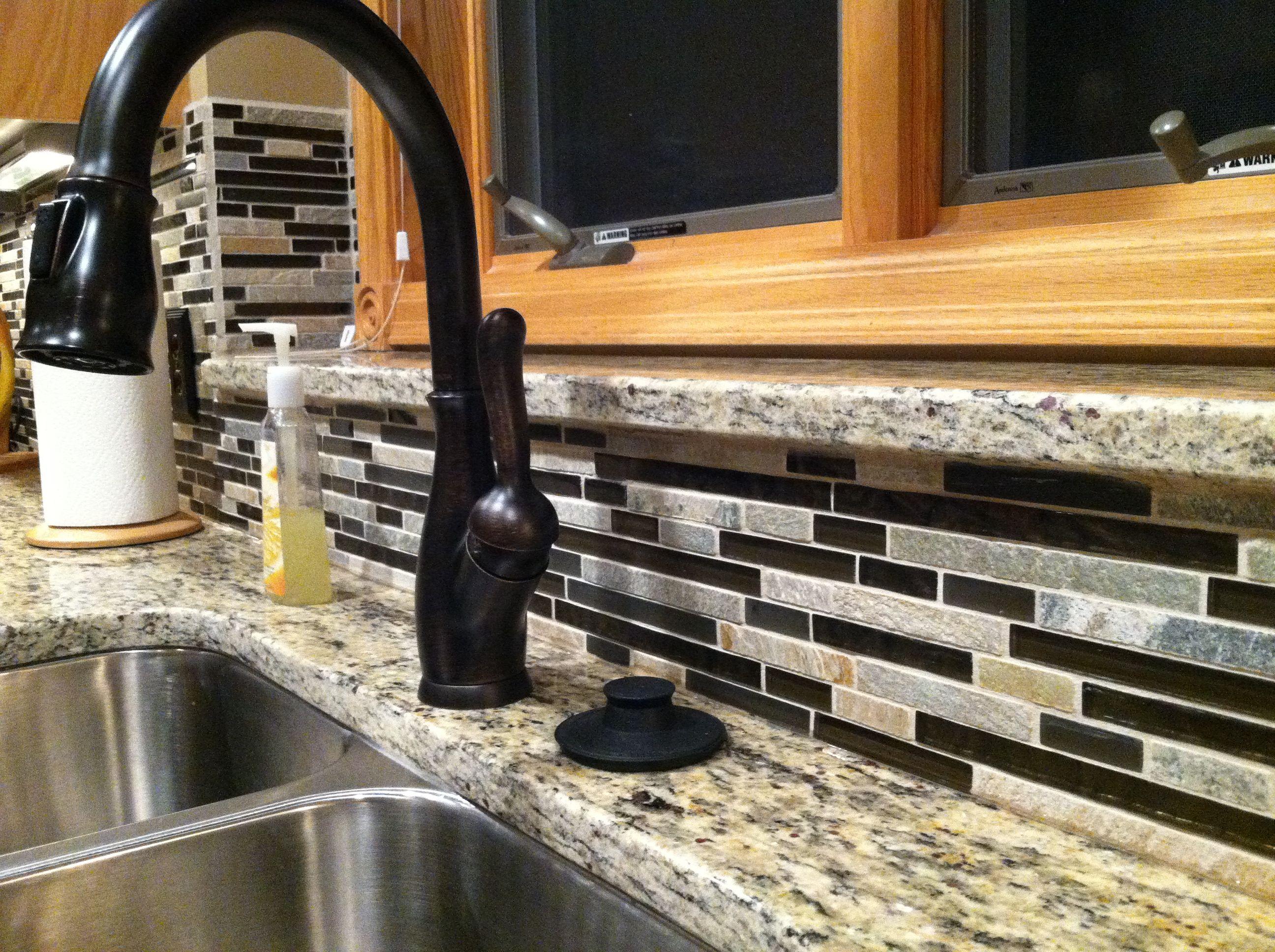 kitchen update delta bronze kitchen faucet Delta oil rubbed bronze faucet Backsplash is glass and stone MC Pacific Foil Slate