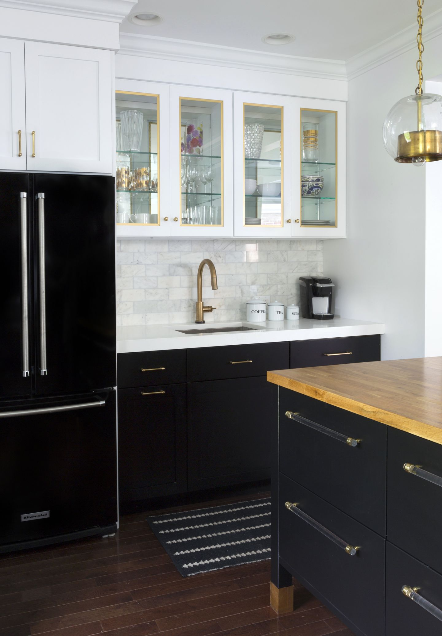 kitchen black cabinets Black refrigerator with black base cabinets and white upper cabinets marble subway tile brass hardware kitchen