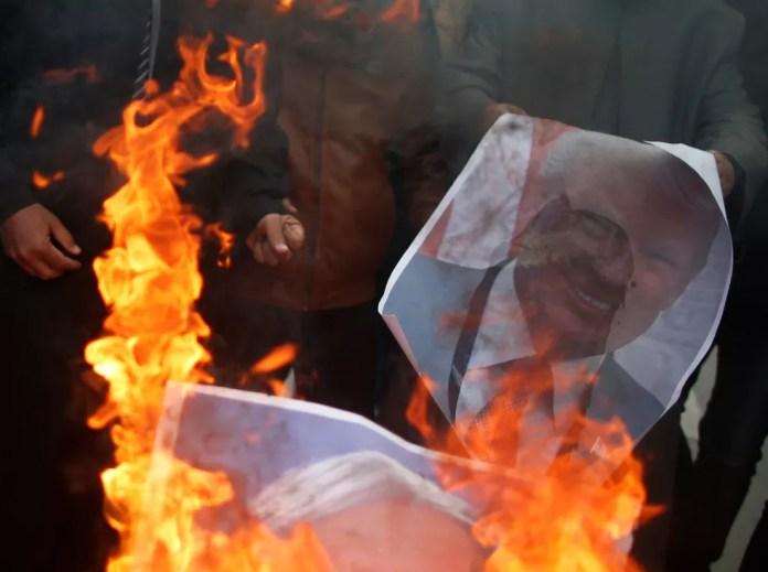 Palestinos queimam imagens de Donald Trump em Gaza, após anúncio de transferência de embaixada (Foto: Mohammed Salem/Reuters)