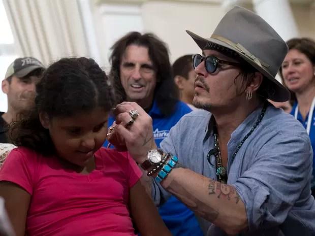 Johnny Depp coloca um aparelho auditivo no ouvido de uma criança, em sua vinda ao Rio (Foto: AP Photo/Silvia Izquierdo)