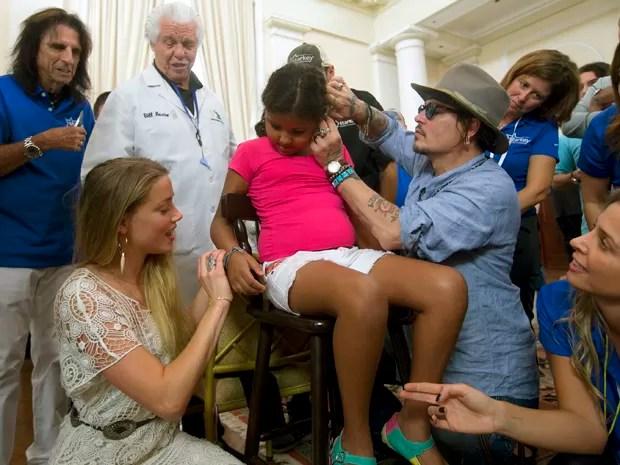 O ator Johnny Depp coloca um aparelho auditivo no ouvido de uma criança enquanto sua mulher, a atriz Amber Heard, dá uma pulseira à criança (Foto: AP Photo/Silvia Izquierdo)