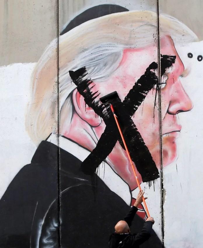 Palestino picha imagem do presidente americano, Donald Trump, pintada no muro que cerca a cidade de Belém, na Cisjordânia, nesta quinta-feira (7) (Foto: Mussa Qawasma/ Reuters)