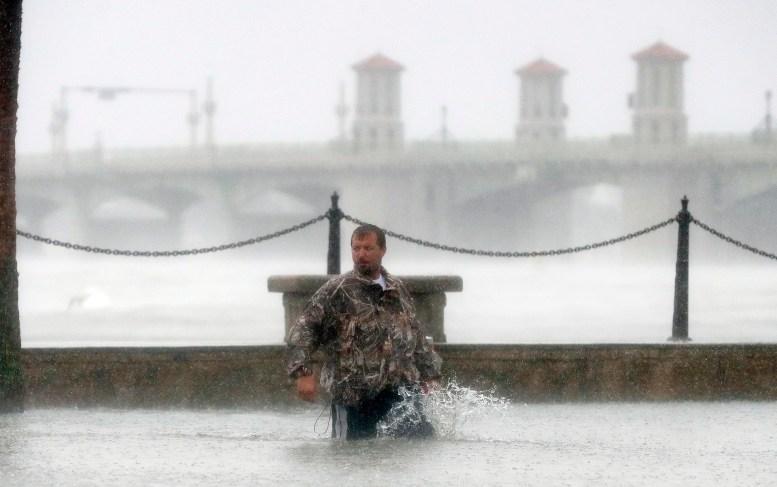 Un hombre trata de caminar con el agua hasta las rodillas en St. Augustine (AP Photo/John Bazemore)