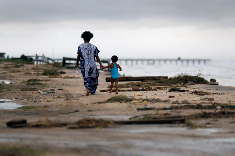 Josephine y Kira Emberton caminan entre los escombros (AP Photo/Eric Gay)