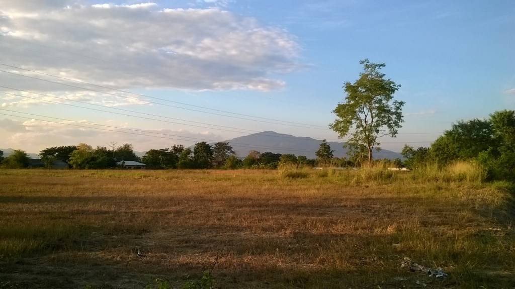 Chiang Mai, Thailand: View of the western hills from the end of our street. The empty land in the foreground is one of the many open spaces in the mu baan which I assume will eventually be built on.