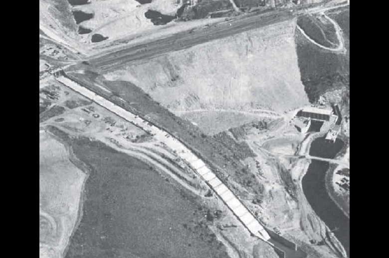 Figure 3. Aerial photo of Teton Dam as it was nearing completion, taken September 26, 1975, before the filling of the reservoir. Star marks approximate position near the right abutment where the leak began. Note the power and pumping station at the base of the dam. Source: After Teton