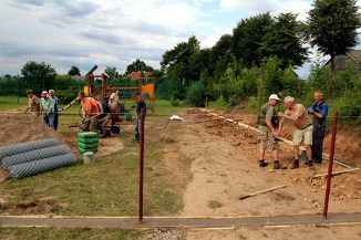 Volunteers installing chain-link fence at playground