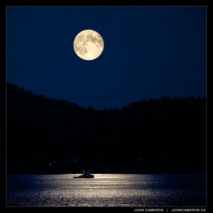 A tug works under a full moon near Pender Islands