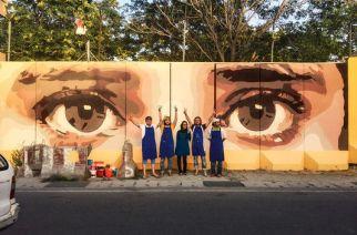 Kabir Mokamel (deuxième en partant de la gauche) avec des membres de son collectif d'artistes devant son premier graffiti, « Je vous vois », qui fait allusion à la corruption dans le pays. OMAID SHARIFI/ARTLORDS
