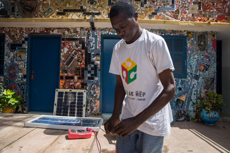 Modou travaille sur son prototype de panneau solaire. CRÉDITS : MATTEO MAILLARD