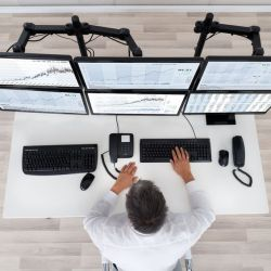 51450113 - rear view of stock market broker looking at graphs at desk in office