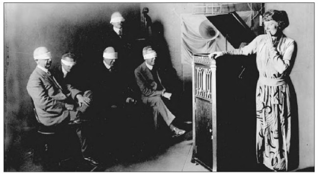 "Soprano Frieda Hempel in a 1919 tone test with ""Edison's musical experts."" Note that the blindfolds also cover their ears"