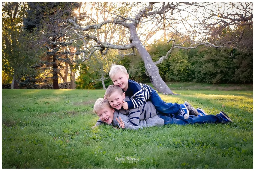 brothers piled on top of each other smiling