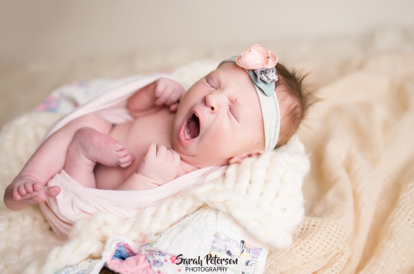 newborn baby girl is yawning