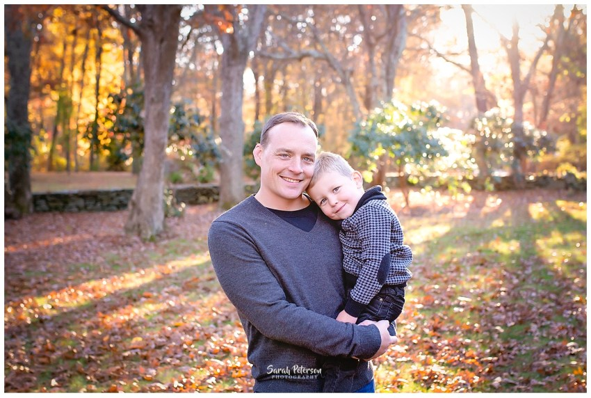 Dad holding son in the fall leaves with sunset behind them