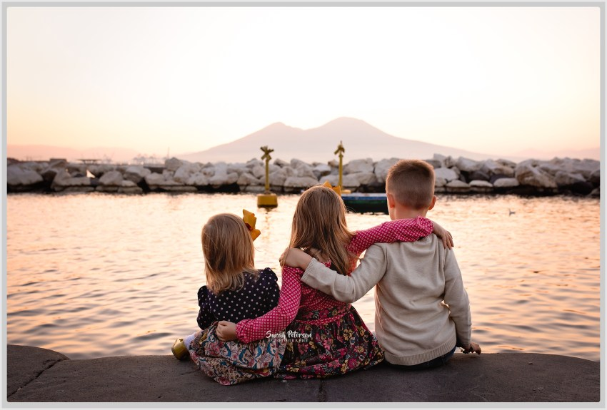 three children looking at Mount Vesuvius sitting by the water during sunrise