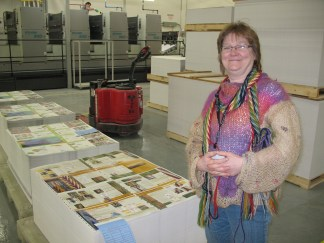 Carol standing beside the printed pages of her book.