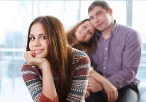 Smiling teenage girl sitting in front of her parents