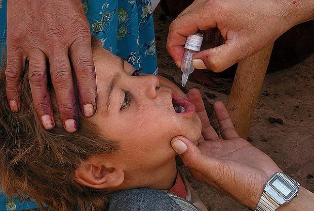 Child taking drops of polio