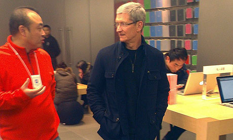 TIm Cook (right) talking to a staff member at an Apple store in Beijing (Credit: Reuters)